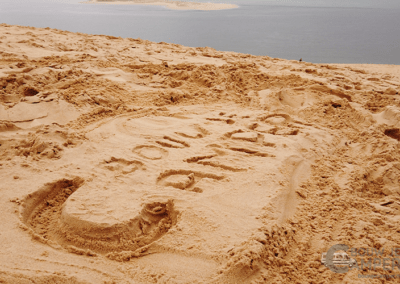 Logo in zand bij Dune du Pilat in Frankrijk